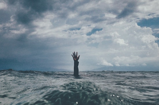 How to deal with overwhelm by Mark Pettit of Lucemi Consulting. Man feeling overwhelmed at sea